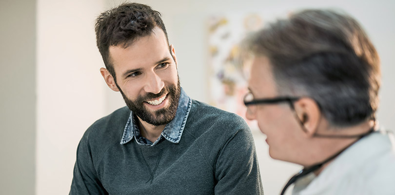 Happy mid adult male patient talking with his doctor.
