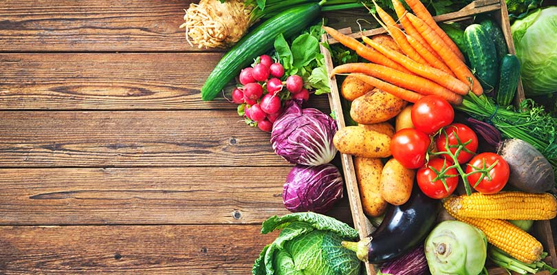 Assortment of the fresh vegetables on rustic wooden table