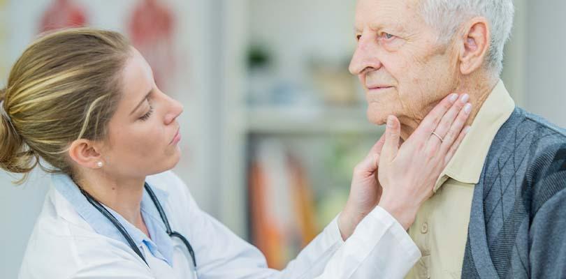 A doctor examining an older man's lymph nodes.