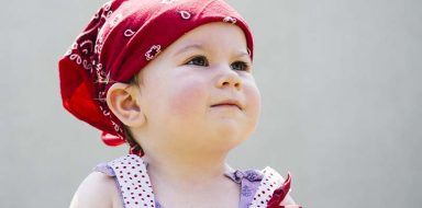 A little girl wearing a red bandanna on her head.