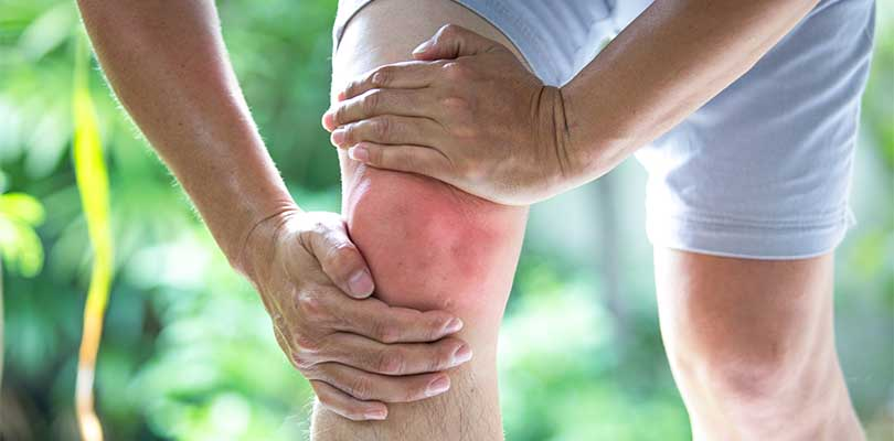 A person outside holding their knee.